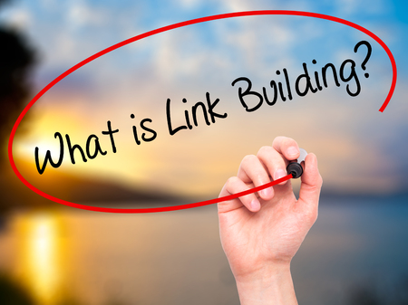 link building: Man Hand writing What is Link Building? with black marker on visual screen. Isolated on nature. Business, technology, internet concept. Stock Photo Stock Photo