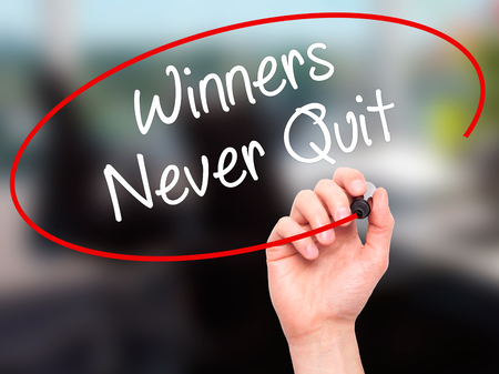 persist: Man Hand writing Winners Never Quit with black marker on visual screen. Isolated on background. Business, technology, internet concept. Stock Photo