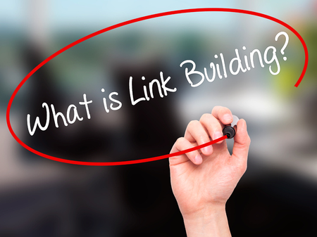 keywords link: Man Hand writing What is Link Building? with black marker on visual screen. Isolated on office. Business, technology, internet concept. Stock Photo