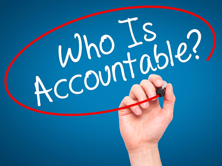 obligated: Man Hand writing Who Is Accountable? with black marker on visual screen. Isolated on blue. Business, technology, internet concept. Stock Image
