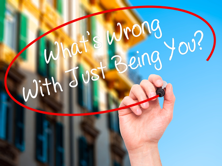 socialization: Man Hand writing Whats Wrong With Just Being You? with black marker on visual screen. Isolated on city. Business, technology, internet concept. Stock Photo