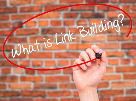 link building: Man Hand writing What is Link Building? with black marker on visual screen. Isolated on bricks. Business, technology, internet concept. Stock Photo Stock Photo