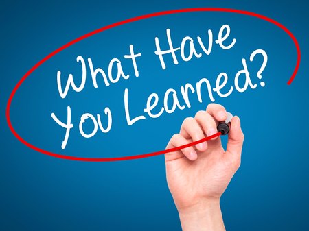 learned: Man Hand writing What Have You Learned? with black marker on visual screen. Isolated on blue. Business, technology, internet concept. Stock Photo