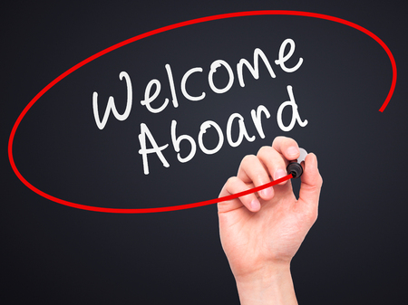 aboard: Man hand writing Welcome Aboard on visual screen. Business,help, internet, technology concept. Isolated on black. Stock Photo