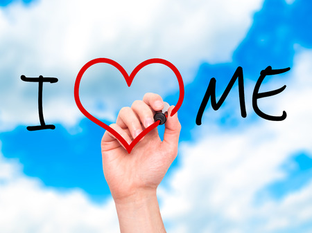egoistic: Man hand writing I Love Me on visual screen. Love, family, internet concept. Isolated on sky. Stock Photo