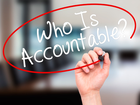 obligate: Man Hand writing Who Is Accountable? with black marker on visual screen. Isolated on office. Business, technology, internet concept. Stock Image
