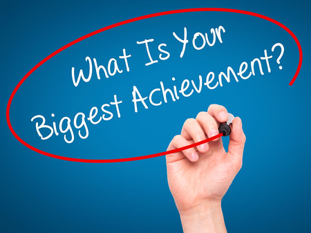 overachieving: Man Hand writing What Is Your Biggest Achievement? with black marker on visual screen. Isolated on background. Business, technology, internet concept. Stock Photo