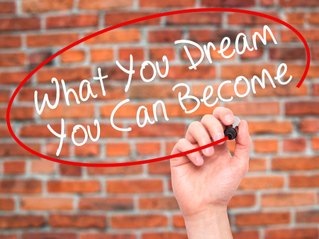 become: Man Hand writing What You Dream You Can Become with black marker on visual screen. Isolated on bricks. Business, technology, internet concept. Stock Photo Stock Photo