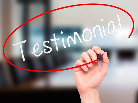 commendation: Man hand writing Testimonial on visual screen. Business, help, internet, technology concept. Isolated on office. Stock Photo