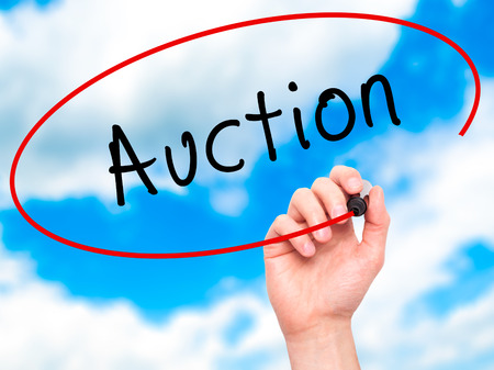 vend: Man Hand writing Auction with black marker on visual screen. Isolated on sky. Business, technology, internet concept. Stock Image Stock Photo