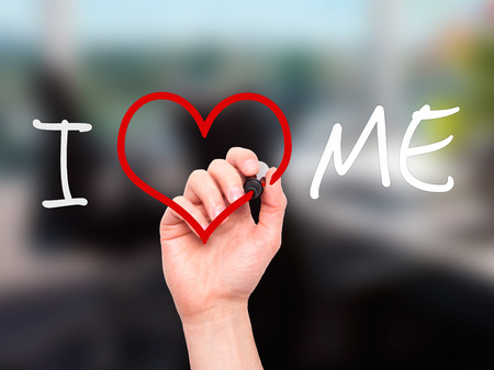 egoistic: Man hand writing I Love Me on visual screen. Love, family, internet concept. Isolated on office. Stock Photo