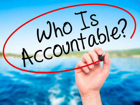 obligated: Man Hand writing Who Is Accountable? with black marker on visual screen. Isolated on nature. Business, technology, internet concept. Stock Image
