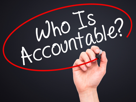 justify: Man Hand writing Who Is Accountable? with black marker on visual screen. Isolated on black. Business, technology, internet concept. Stock Image Stock Photo