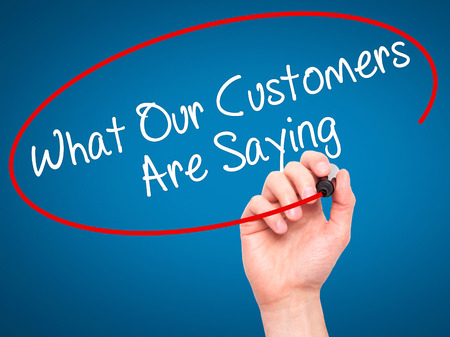 Man Hand writing What Our Customers Are Saying with black marker on visual screen. Isolated on blue. Business, technology, internet concept. Stock Photo