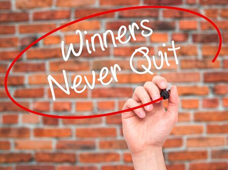 not give: Man Hand writing Winners Never Quit with black marker on visual screen. Isolated on background. Business, technology, internet concept. Stock Photo
