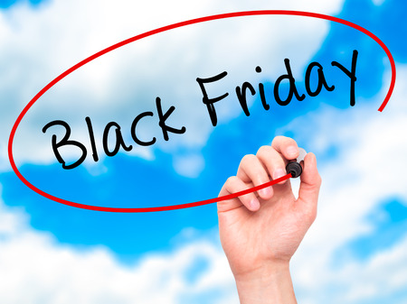 writing black: Man Hand writing Black Friday with black marker on visual screen. Isolated on sky. Business, technology, internet concept. Stock Image