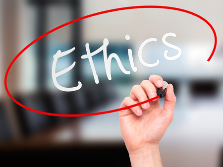uprightness: Man hand writing Ethics on visual screen. Business,help, internet, technology concept. Isolated on office. Stock Photo
