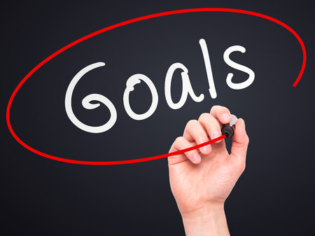 intend: Man hand writing Goals on visual screen. Business,help, internet, technology concept. Isolated on black. Stock Photo Stock Photo