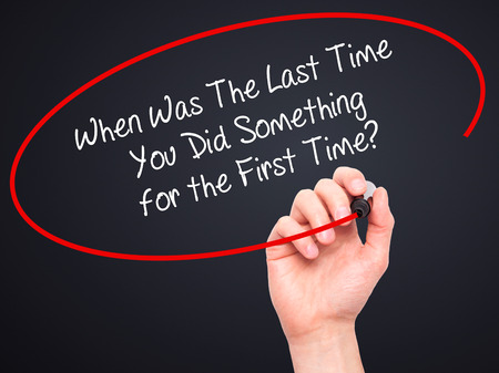 promptness: Man Hand writing When Was The Last Time You Did Something for the First Time? with black marker on visual screen. Isolated on black. Business, technology, internet concept. Stock Photo