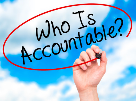justify: Man Hand writing Who Is Accountable? with black marker on visual screen. Isolated on sky. Business, technology, internet concept. Stock Image Stock Photo