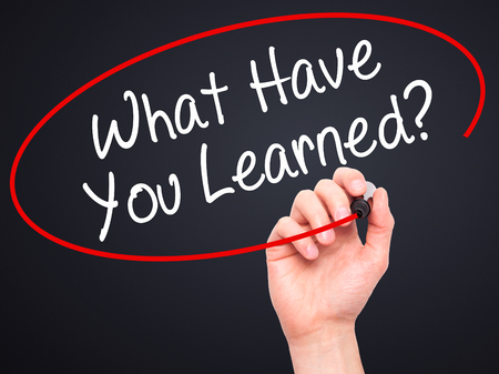 learned: Man Hand writing What Have You Learned? with black marker on visual screen. Isolated on black. Business, technology, internet concept. Stock Photo Stock Photo