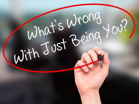 individualism: Man Hand writing Whats Wrong With Just Being You? with black marker on visual screen. Isolated on office. Business, technology, internet concept. Stock Photo Stock Photo