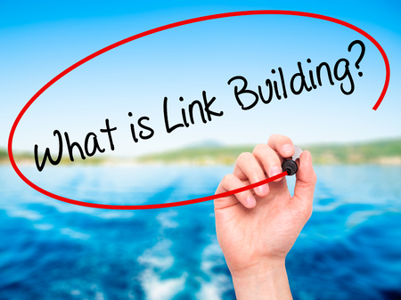 wiki: Man Hand writing What is Link Building? with black marker on visual screen. Isolated on nature. Business, technology, internet concept. Stock Photo Stock Photo