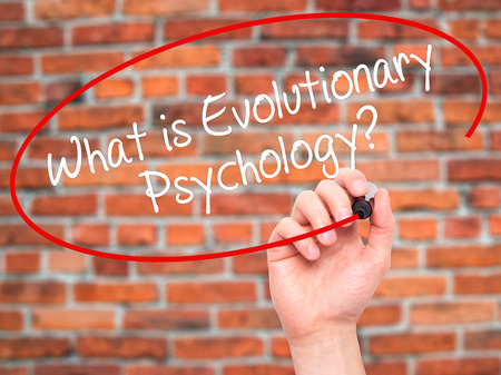 Man Hand writing What is Evolutionary Psychology? with black marker on visual screen. Isolated on background. Business, technology, internet concept. Stock Photo