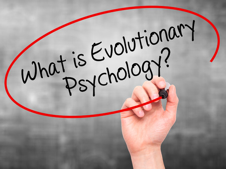 evolutionary: Man Hand writing What is Evolutionary Psychology? with black marker on visual screen. Isolated on background. Business, technology, internet concept. Stock Photo