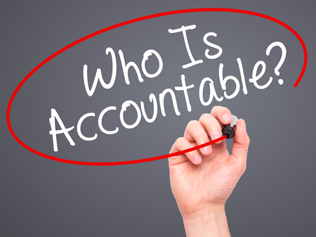 justify: Man Hand writing Who Is Accountable? with black marker on visual screen. Isolated on grey. Business, technology, internet concept. Stock Image