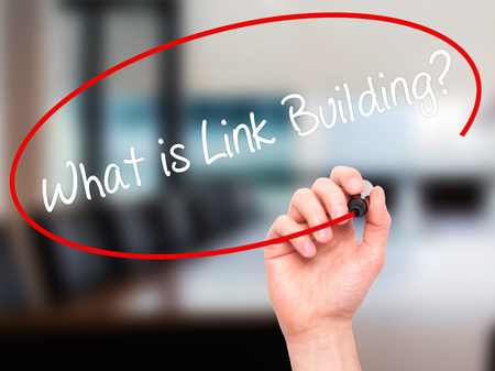wiki: Man Hand writing What is Link Building? with black marker on visual screen. Isolated on office. Business, technology, internet concept. Stock Photo
