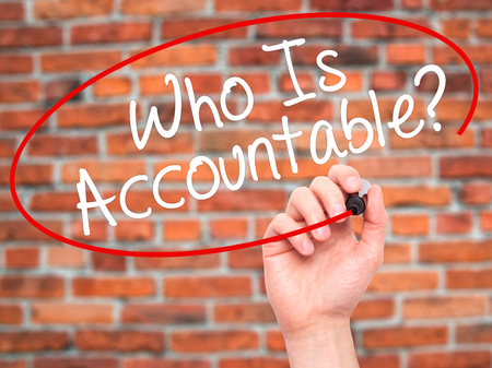 obligate: Man Hand writing Who Is Accountable? with black marker on visual screen. Isolated on bricks. Business, technology, internet concept. Stock Image