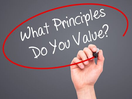 morals: Man Hand writing What Principles Do You Value? with black marker on visual screen. Isolated on grey. Business, technology, internet concept. Stock Photo