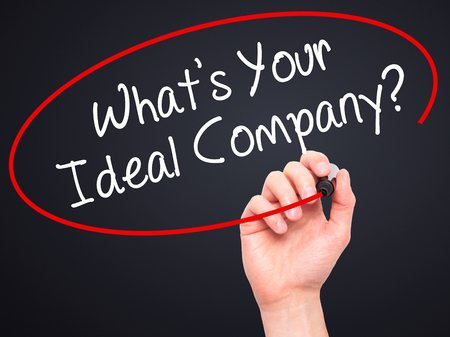 fulfilled: Man Hand writing Whats Your Ideal Company? with black marker on visual screen. Isolated on background. Business, technology, internet concept. Stock Photo