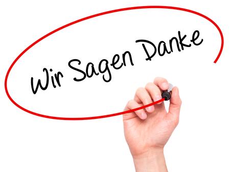 Man Hand schrijven Wir Sagen Danke (We hebben bedankt in het Duits) met zwarte stift op visuele scherm. Geïsoleerd op wit. Business, technologie, internet concept. Stock foto