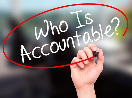 culpable: Man Hand writing Who Is Accountable? with black marker on visual screen. Isolated on office. Business, technology, internet concept. Stock Image