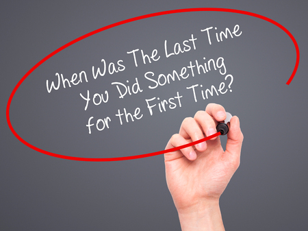 promptness: Man Hand writing When Was The Last Time You Did Something for the First Time? with black marker on visual screen. Isolated on grey. Business, technology, internet concept. Stock Photo