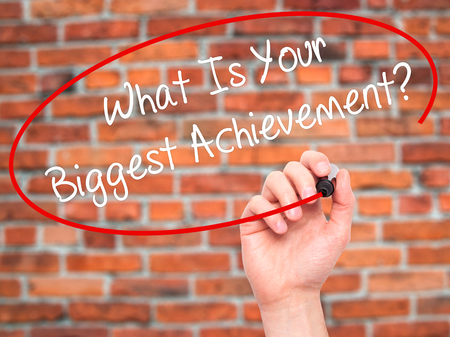 exceeding: Man Hand writing What Is Your Biggest Achievement? with black marker on visual screen. Isolated on background. Business, technology, internet concept. Stock Photo
