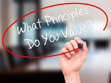 morals: Man Hand writing What Principles Do You Value? with black marker on visual screen. Isolated on office. Business, technology, internet concept. Stock Photo