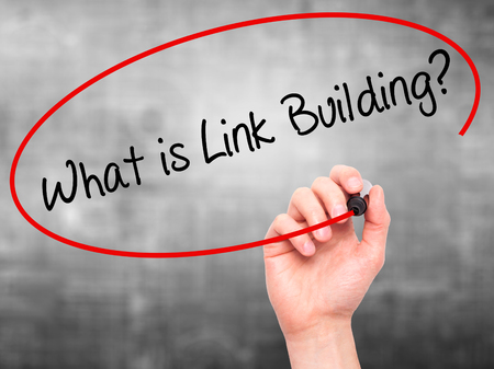 keywords link: Man Hand writing What is Link Building? with black marker on visual screen. Isolated on grey. Business, technology, internet concept. Stock Photo