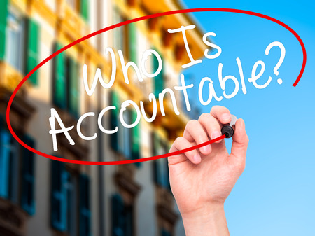 justify: Man Hand writing Who Is Accountable? with black marker on visual screen. Isolated on city. Business, technology, internet concept. Stock Image Stock Photo