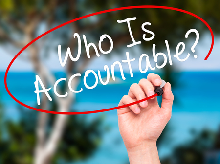 justify: Man Hand writing Who Is Accountable? with black marker on visual screen. Isolated on nature. Business, technology, internet concept. Stock Image
