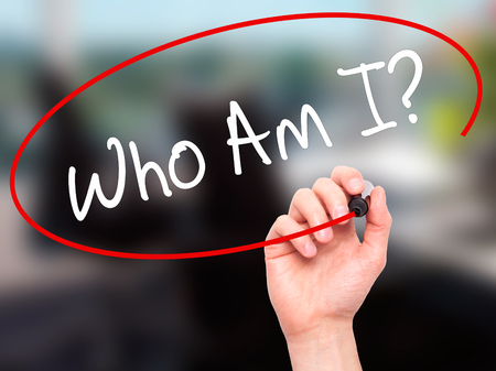 Man Hand writing Who Am I? with black marker on visual screen. Isolated on office. Business, technology, internet concept. Stock Photo