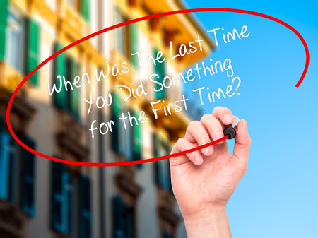 promptness: Man Hand writing When Was The Last Time You Did Something for the First Time? with black marker on visual screen. Isolated on city. Business, technology, internet concept. Stock Photo Stock Photo