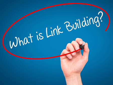 link building: Man Hand writing What is Link Building? with black marker on visual screen. Isolated on blue. Business, technology, internet concept. Stock Photo