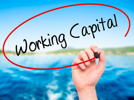 obligations: Man Hand writing Working Capital with black marker on visual screen. Isolated on nature. Business, technology, internet concept. Stock Photo