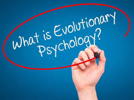 health answers: Man Hand writing What is Evolutionary Psychology? with black marker on visual screen. Isolated on background. Business, technology, internet concept. Stock Photo