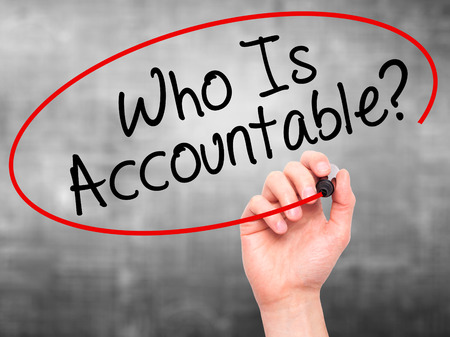 obligated: Man Hand writing Who Is Accountable? with black marker on visual screen. Isolated on grey. Business, technology, internet concept. Stock Image