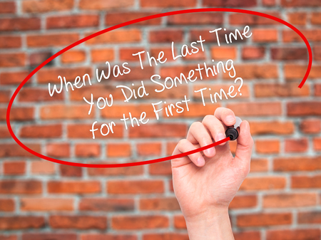 promptness: Man Hand writing When Was The Last Time You Did Something for the First Time? with black marker on visual screen. Isolated on bricks. Business, technology, internet concept. Stock Photo
