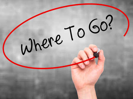 where to go: Man Hand writing Where To Go? with black marker on visual screen. Isolated on background. Business, technology, internet concept. Stock Photo
